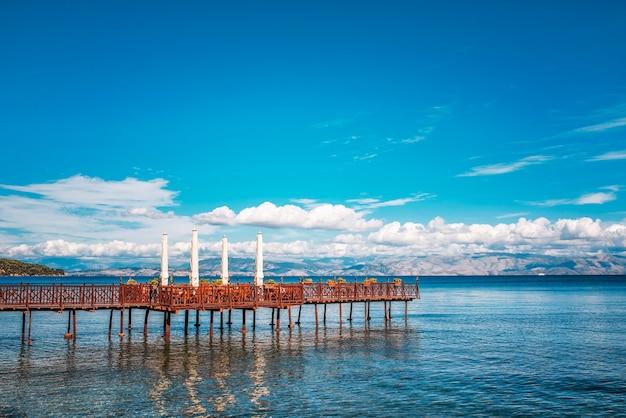 이오니아 해 끝에 낭만적 인 카페가있는 긴 목재 부두. 그리스. 아름다운 자연 환경, sealine에 산. 코르푸 섬에 구름과 화창한 날입니다.