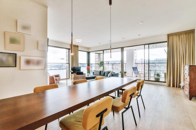 スタイリッシュなインテリアデザインのモダンなオープンスペースのアパートのダイニングゾーンに配置された長い木製のテーブルと椅子
