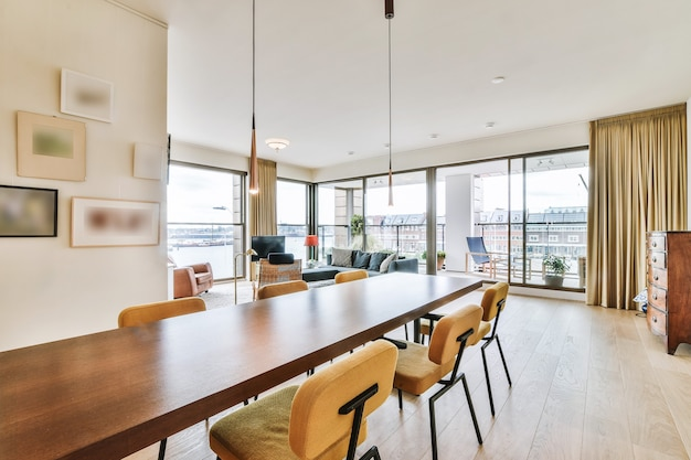 Long wooden table and chairs placed in dining zone of modern open space apartment with stylish interior design