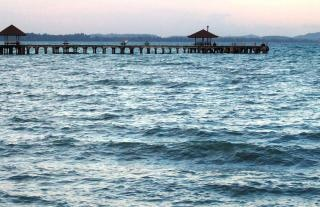 Long wooden tropical pier at sunset