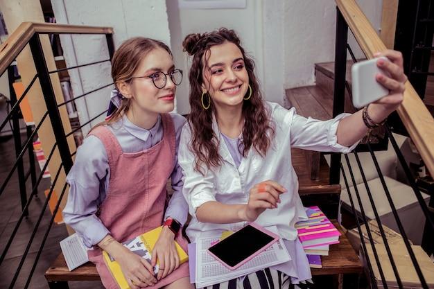 長い労働日。本と木製の階段に座ってスマートフォンで自分撮りを作るきれいな女性の笑顔