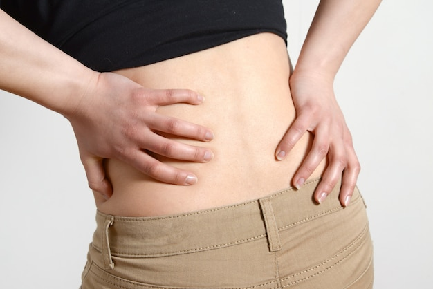 長時間労働と健康。腰痛を持つ若い女性。灰色の背中の痛みを持つ女性
