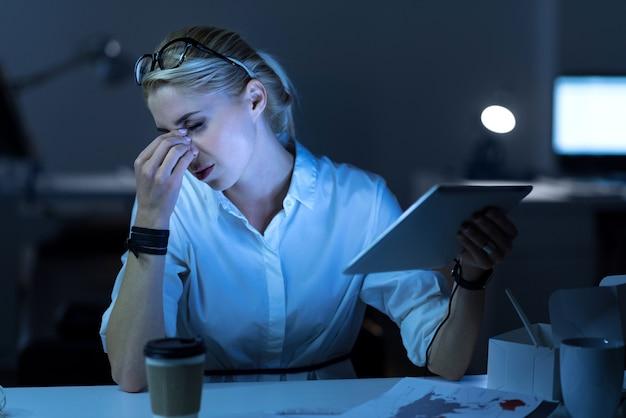 긴 근무 시간. 사무실에 앉아 태블릿을 들고 프로젝트를 진행하고 머리를 만지는 동안 지친 피곤한 it 여성