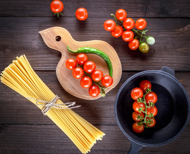 Long yellow raw spaghetti and red cherry tomatoes