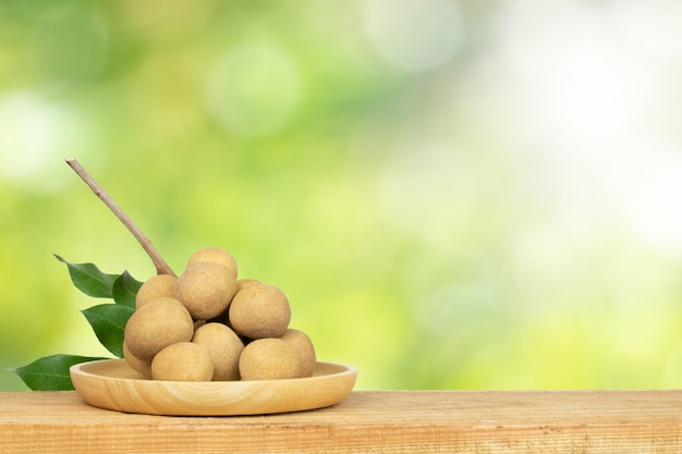 Longan fruit on table and green nature  blurlight background