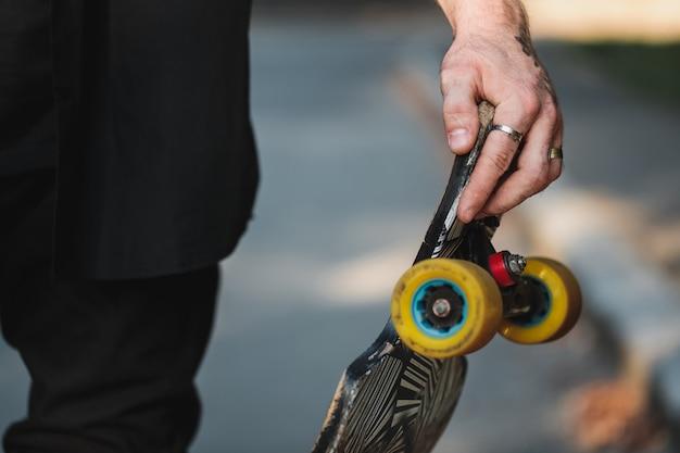 ロングボードのクローズアップ。男の手でスケート。高品質の写真