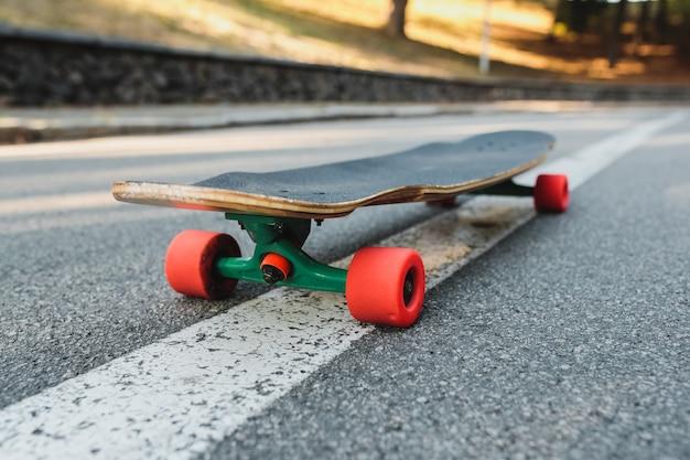 アスファルトに赤い車輪が付いたロングボード。高品質の写真