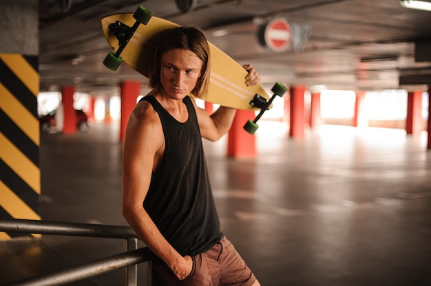 Привлекательный длинноволосый парень смотрит в сторону и держит longboard