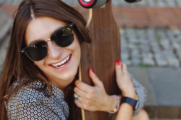Закройте вверх по портрету красивой молодой женщины сидя на том основании и держа longboard в погоде улицы города солнечной.