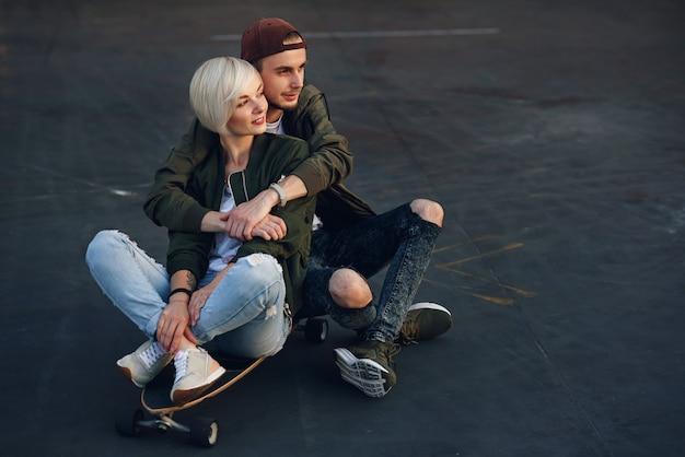 Молодая очаровательная пара в любви, сидя на longboard скейтборде на крыше промышленного здания на закате.