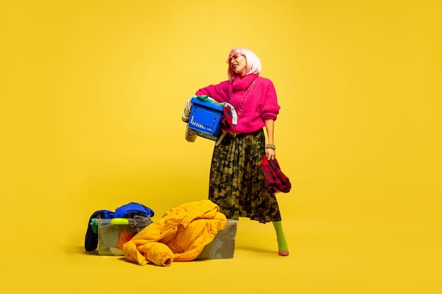 Longer laundry with collection of clothes. caucasian woman's portrait on yellow background.