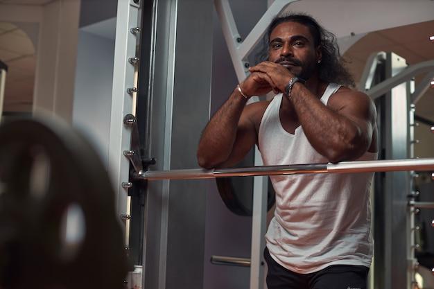 長い髪のひげを生やした筋肉質の男は、運動器具の近くのジムに立っています。