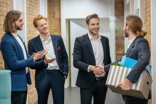 Длинноволосый мужчина в костюме с коробкой личных вещей и трое радостных коллег в офисе