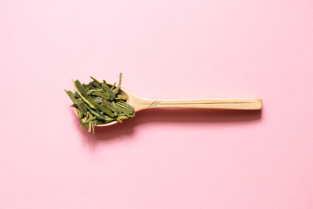 Longjing. chinese leaf green tea in a spoon on a pink background.
