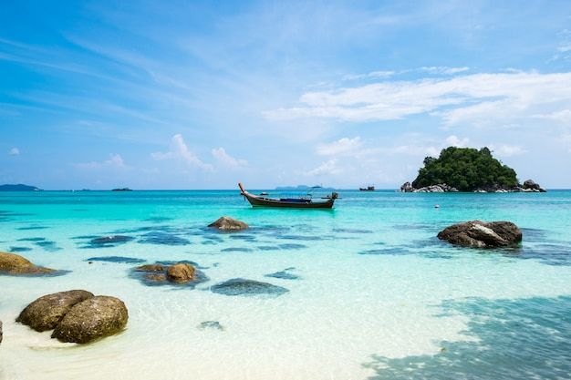 Longtail boat on crystal sea white sand
