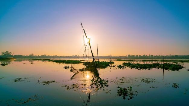 釣りtrap付きロングテールボート朝日の日の出の湖の美しい景色。