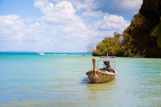 熱帯の砂浜の海岸に係留された製品や商品を運ぶロングテールボート