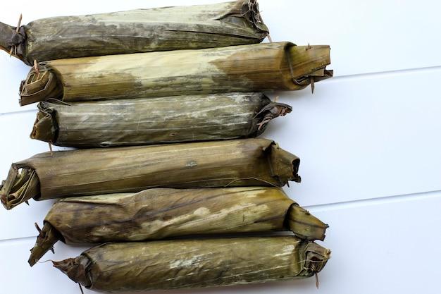 Лонтонг, индонезийский прессованный рисовый пирог в форме цилиндра, завернутого в банановый лист. обычно подается с саюром, гадо-гадо или песелем. вид сверху с копией пространства