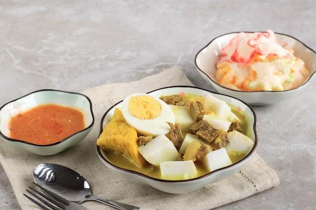 ロントンカリサピまたはインドネシアビーフカレーとライスケーキ。インドネシアの西ジャワで朝食に人気の屋台の食べ物。サンバルとクラッカー、コピースペースを添えて
