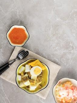 ロントンカリサピまたはインドネシアビーフカレーとライスケーキ。インドネシアの西ジャワで朝食に人気の屋台の食べ物。上面図、コピースペース