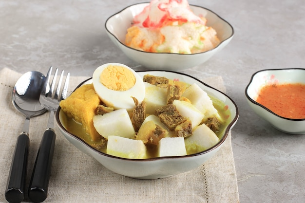 ロントンカリサピまたはインドネシアビーフカレーとライスケーキ。インドネシア、西ジャワで朝食に人気の屋台の食べ物
