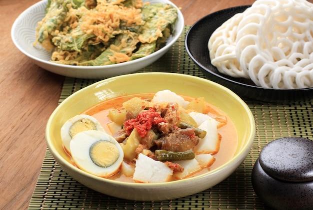 Лонтонг саюр паданг, овощное карри с рисовым пирогом, подается с вареным яйцом. подается на деревянном столе с желтой тарелкой. подается с крупуком варунгом на заднем плане
