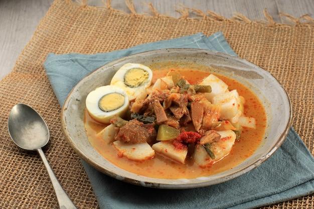 Лонтонг саюр паданг, овощное карри с рисовым пирогом, подается с вареным яйцом