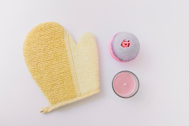 Loofah mitt; bath bomb and candle on white background