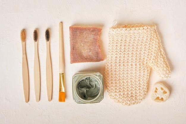 Люфа, мыло, голубая глина в стеклянной банке, щетка, мочалка и бамбуковые зубные щетки на бежевом фоне, место для копирования