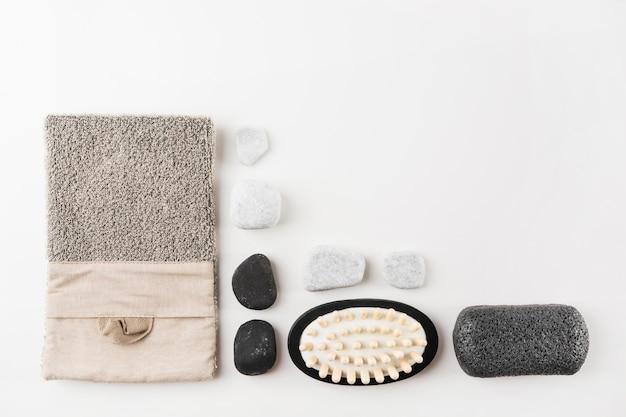 수세미외; 스파 스톤; 마사지 브러시와 경 석 돌 흰색 배경에 고립