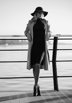 Look amazing at any age. a 40-year-old woman in a coat walks along the embankment.