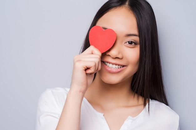Look around, and you will find you love! beautiful young asian woman holding heart shaped valentine card in front of her eye and smiling while standing against grey background