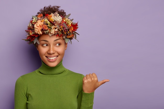 Look aside. joyful tender curly woman wears autumn wreath around head, points away on copy space, smiles pleasantly