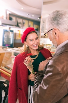 夫を見てください。彼女と話している彼女の夫を見ている素敵なネックレスを身に着けている美しいフランス人女性
