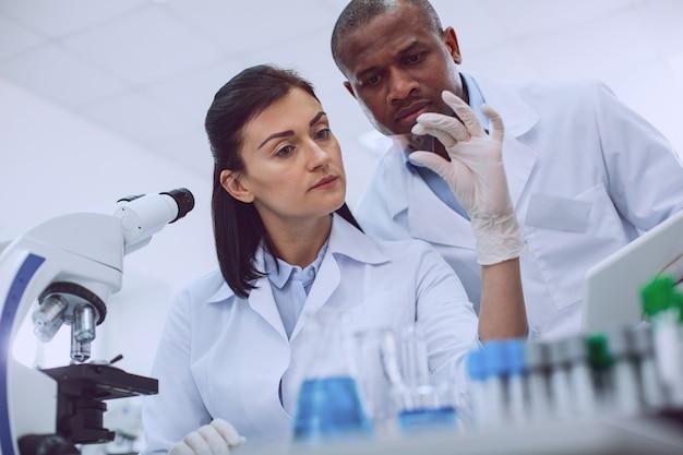 보세요. 샘플을보고있는 웃지 않는 경험이 풍부한 연구원과 그녀의 뒤에 서있는 동료