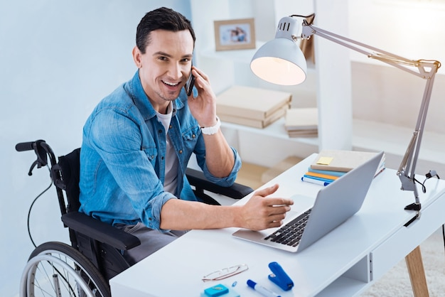 Смотри на меня. веселая брюнетка с улыбкой на лице и взглядом вверх, сидя в инвалидной коляске