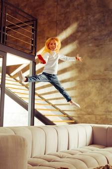 私を見て。ソファでジャンプしながら笑顔を保つ陽気な子供
