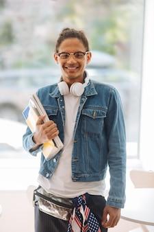 私を見て。右手に本を持って笑顔を保つうれしそうな若い男性