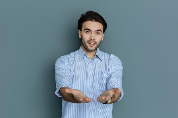 私を見て。灰色の背景に立っている間彼の手を伸ばしてあなたにそれらを見せて素敵なポジティブな魅力的な男