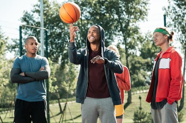 날 봐. 공을 회전하는 방법을 보여 주면서 친구들 앞에 서있는 긍정적 인 쾌활한 남자