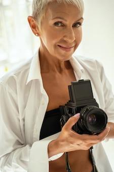 Смотри на меня. красивая женщина улыбается и держит фотоаппарат обеими руками