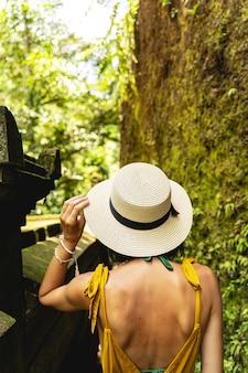 私を見て。苔で覆われた岩を見ながらカメラに背を向けて立っている若い女性