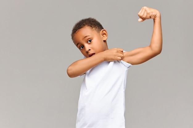 내 이두근을 봐. 그의 긴장된 팔 근육을 보여주는 소매를 당기는 회색 벽에 고립 된 캐주얼 흰색 티셔츠 포즈에서 재미있는 아프리카 계 미국인의 그림. 어린 시절, 피트니스 및 스포츠 개념