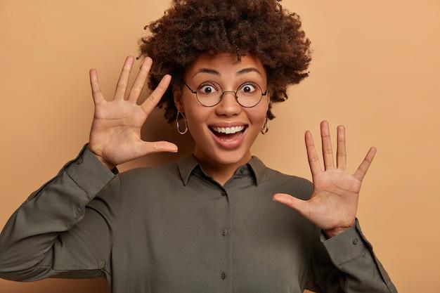 내 깨끗한 손 좀 봐. 긍정적 인 장난기있는 여성은 넓게 미소를 지으며 손바닥을 위로 들어 올리며 즐겁게 미소를 짓습니다.