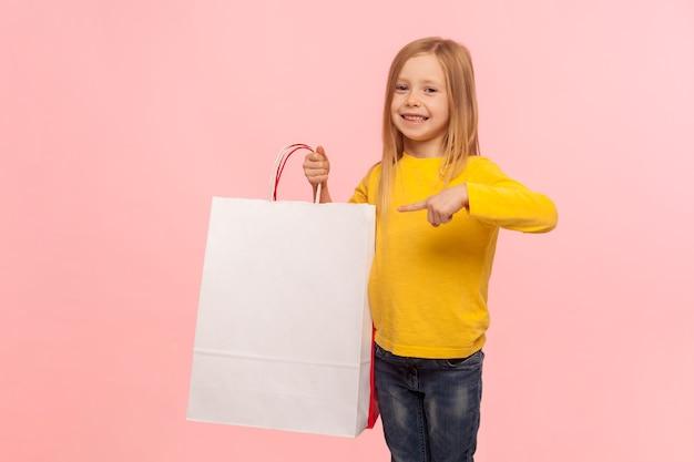 내 구매를 봐. 쇼핑백을 가리키고 카메라를 보며 웃고 있는 매력적인 행복한 어린 소녀의 초상화, 블랙 프라이데이 할인, 저렴한 가격에 만족합니다. 분홍색 배경에 고립 된 스튜디오 촬영