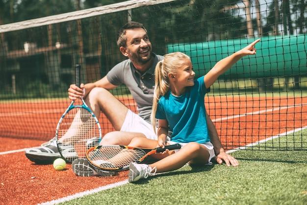Посмотри на это! веселые отец и дочь, опираясь на теннисную сетку и с улыбкой глядя в сторону, сидят на теннисном корте