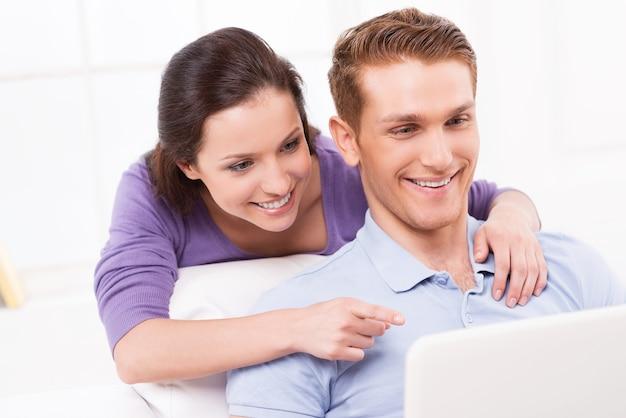 저것 봐! 쾌활한 젊은 부부는 소파에 앉아 노트북을 바라보며 모니터를 가리키며 웃고 있습니다.