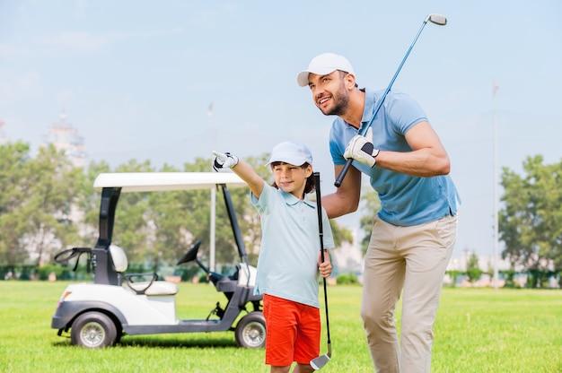 Посмотри на это! веселый молодой человек обнимает своего сына и смотрит в сторону, стоя на поле для гольфа