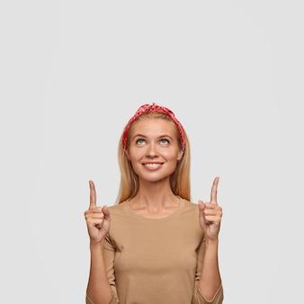 その方向を見てください。広く優しい笑顔で美しい陽気な金髪の若い女性は、上向きで、何か面白いことをしている、白い壁に立って、カジュアルな服を着ています。
