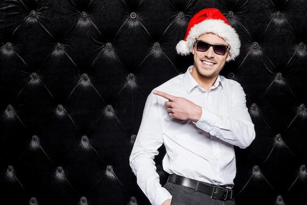 저것 봐! 선글라스와 산타 모자를 쓴 잘생긴 청년이 검은 배경에 서서 멀리 가리키며 웃고 있다